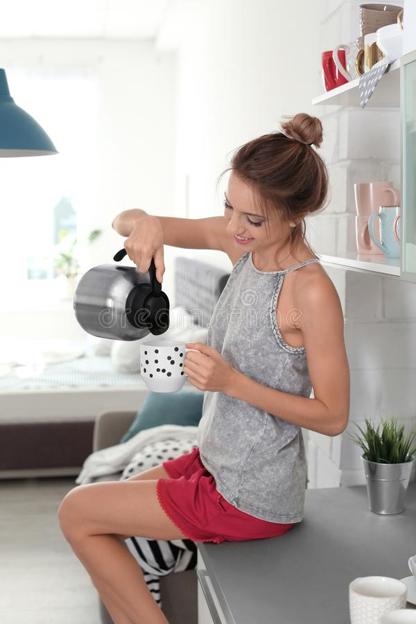 Beautiful young woman pouring tea into cup in kitchen at home. Lazy morning stock photo