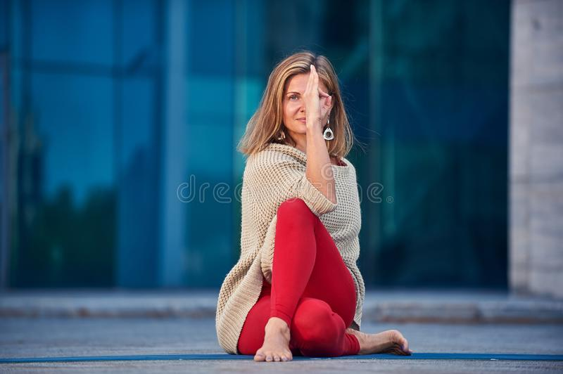 Beautiful young woman practices yoga asana Gomukhasana - Cow Face pose outdoors against the background of a modern city.  stock photo