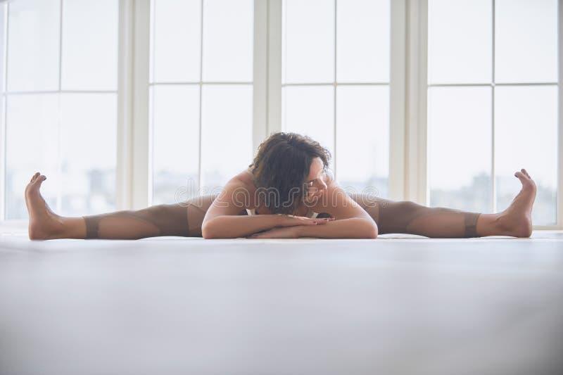 Beautiful young woman practices yoga asana Samakonasana Straight angle posture in the light yoga studio royalty free stock photos