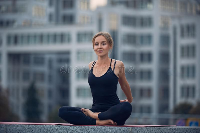 Beautiful young woman practices yoga asana Sukhasana - The Easy Sitting crosslegged Pose outdoors against the background of a mode. Rn city royalty free stock images