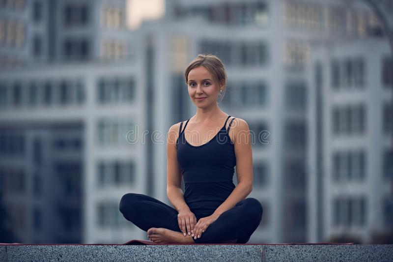 Beautiful young woman practices yoga asana Sukhasana - The Easy Sitting crosslegged Pose outdoors against the background of a mode. Rn city stock images