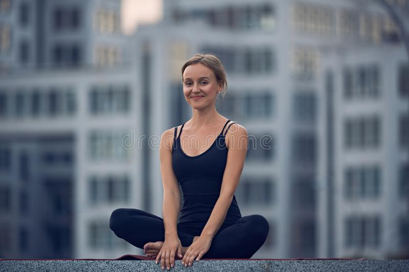 Beautiful young woman practices yoga asana Sukhasana - The Easy Sitting crosslegged Pose outdoors against the background of a mode. Rn city stock photos