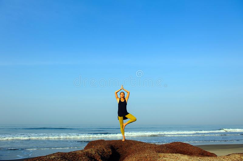 Beautiful young woman practicing yoga and stretching exercises at the summer ocean beach stock images