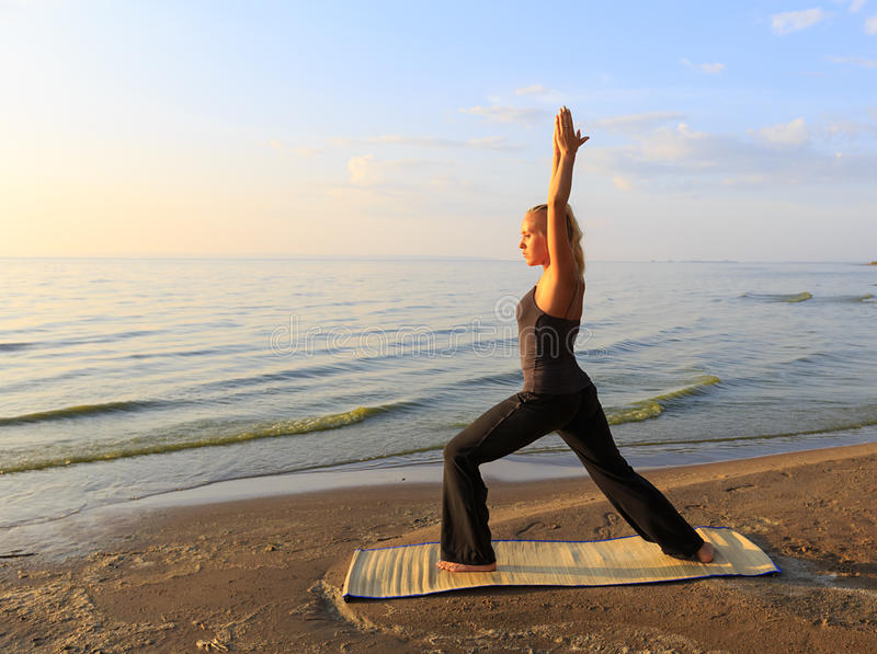 Beautiful young woman practising yoga on mat outdoors at river bank on sand at sunset stock photos