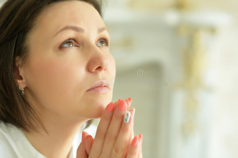 Portrait of beautiful young woman praying and posing at home stock image
