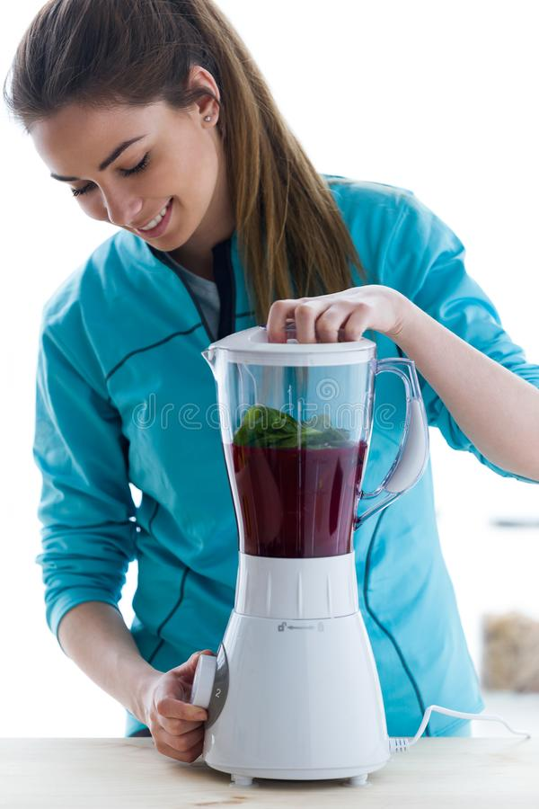 Beautiful young woman preparing detox juice in the blender at home. stock photo