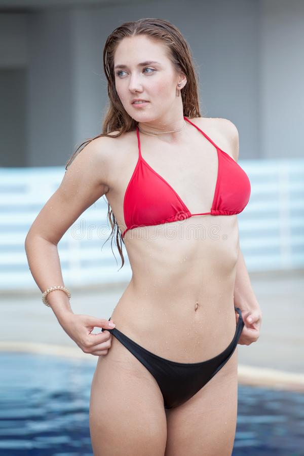 beautiful young woman pulling bikini .standing and posing on swimming pool .sexy female in a swimsuit resting in vacation stock photography