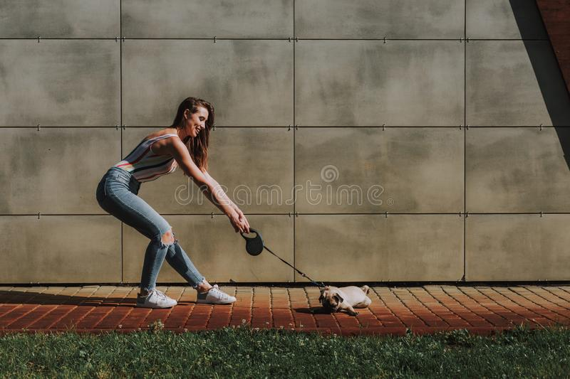 Young lady is pulling on leash her little puppy stock photography