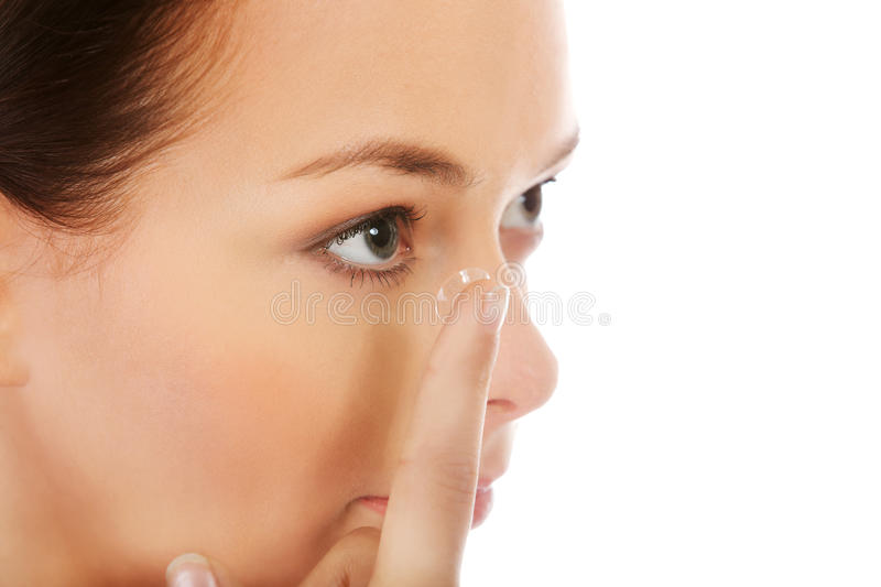 Beautiful young woman putting a contact lens stock images