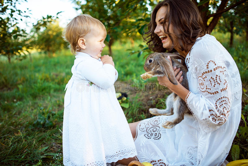 Beautiful young woman with with rabbit and little cute girl stock images