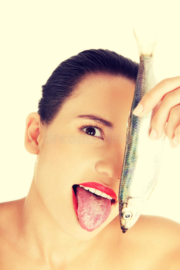 Beautiful young woman with raw fish.  royalty free stock image