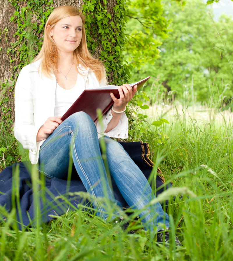 Beautiful young woman reading a book stock photos