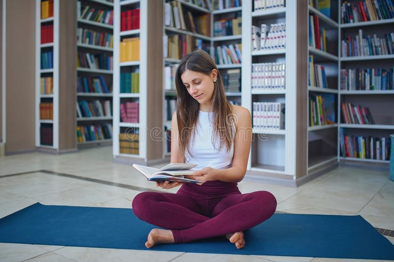 Beautiful young woman reading book and practices yoga asana Sukhasana - The Easy Sitting crosslegged Pose in the library.  stock images
