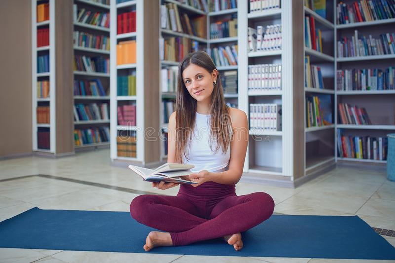 Beautiful young woman reading book and practices yoga asana Sukhasana - The Easy Sitting crosslegged Pose in the library.  royalty free stock photos