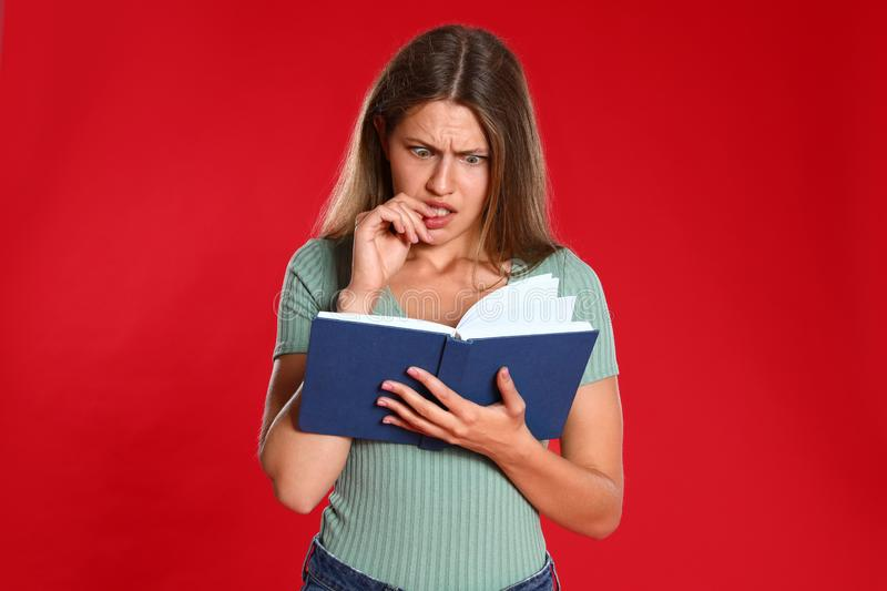 Beautiful young woman reading book on red royalty free stock image