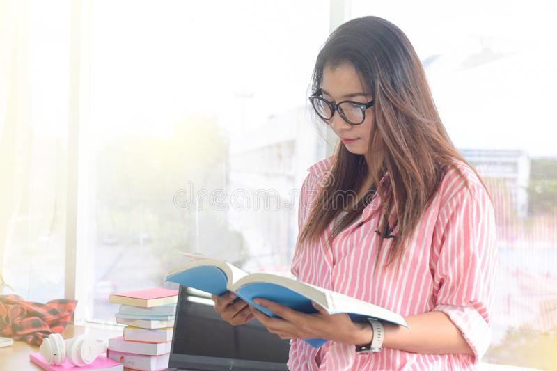 Beautiful young woman reading a book to find out information in the library. people, knowledge, education and school concept royalty free stock photo