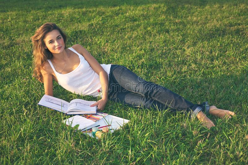 Beautiful young woman reading on a green meadow royalty free stock image