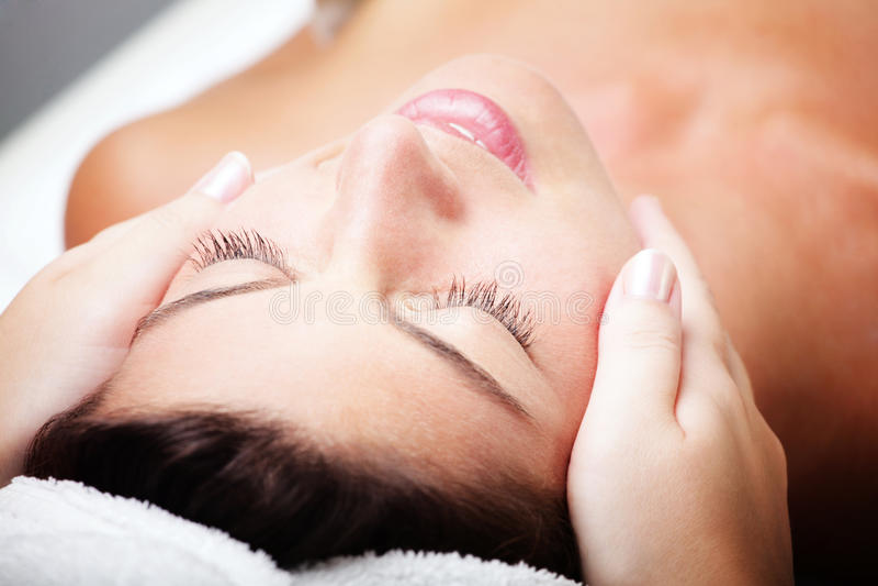 Beautiful young woman receiving facial massage. Close-up of a beautiful young woman receiving facial massage stock image