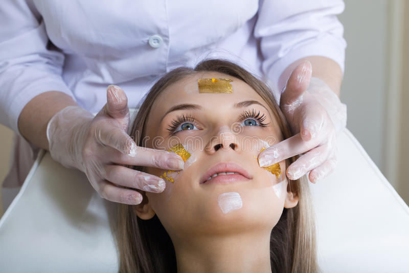 Beautiful young woman receiving facial massage royalty free stock photos