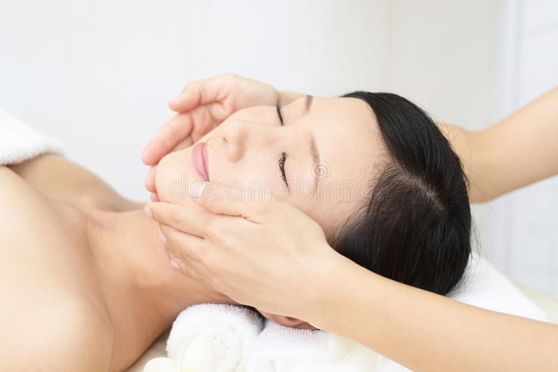 Beautiful young woman receiving facial massage stock photo