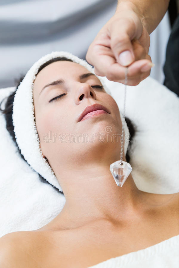 Beautiful young woman receiving gemstone therapy in spa. stock photo