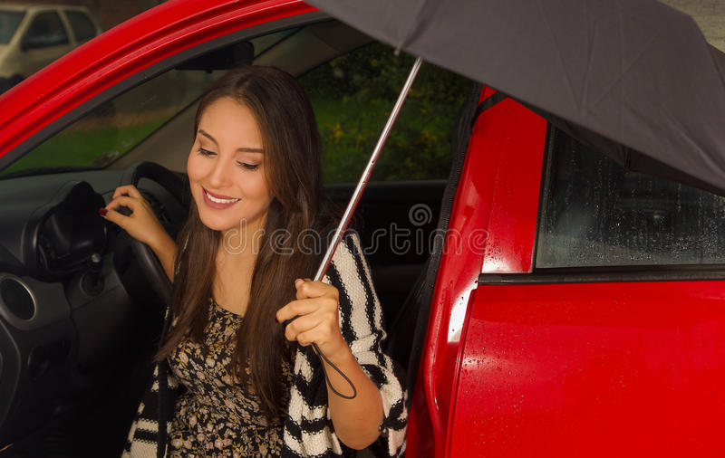Beautiful young woman in red car wearing a wool jacket and posing for camera and holding an umbrella.  stock image
