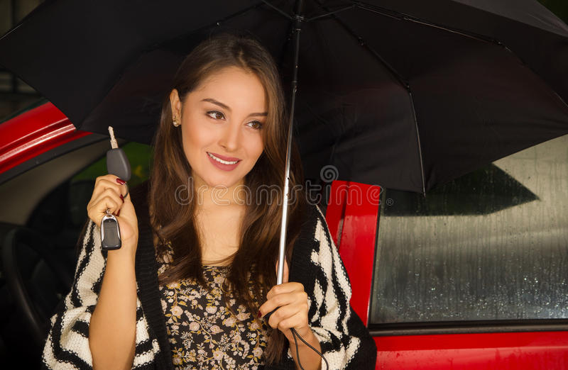 Beautiful young woman in red car wearing a wool jacket and posing for camera while she is holding an umbrella with one. Hand and holding her keys with her other stock photos