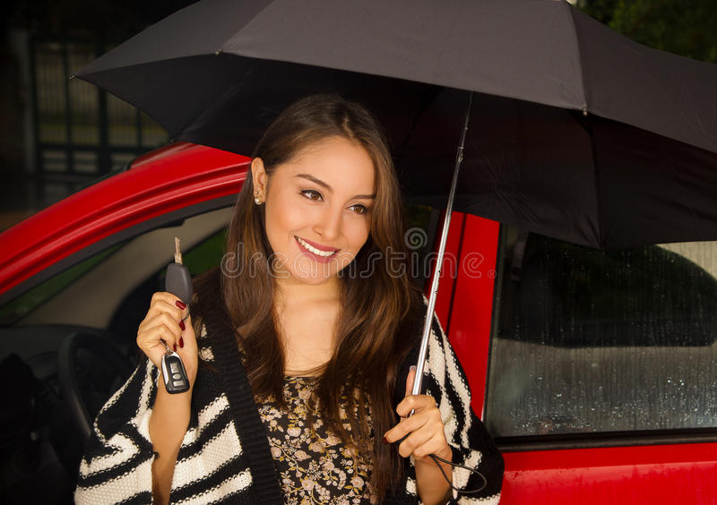Beautiful young woman in red car wearing a wool jacket and posing for camera while she is holding an umbrella with one. Hand and holding her keys with her other stock photography
