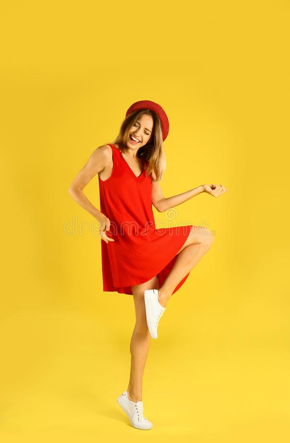 Beautiful young  in red dress dancing on yellow background royalty free stock photos