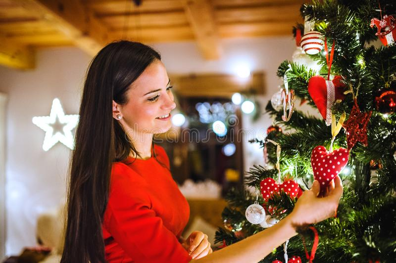Young woman in front of Christmas tree decorating it royalty free stock photo