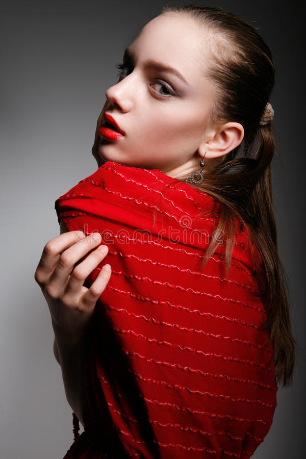 Beautiful young woman in red dress hugging herself. Close-up of beautiful young woman in red dress, with ponytail, bright make-up and jewelry, hugging herself stock photography
