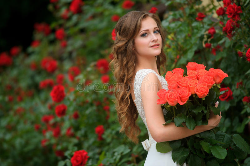 Beautiful young woman with red flowers posing in the rose garden. The Beautiful young woman with red flowers posing in the rose garden stock photo