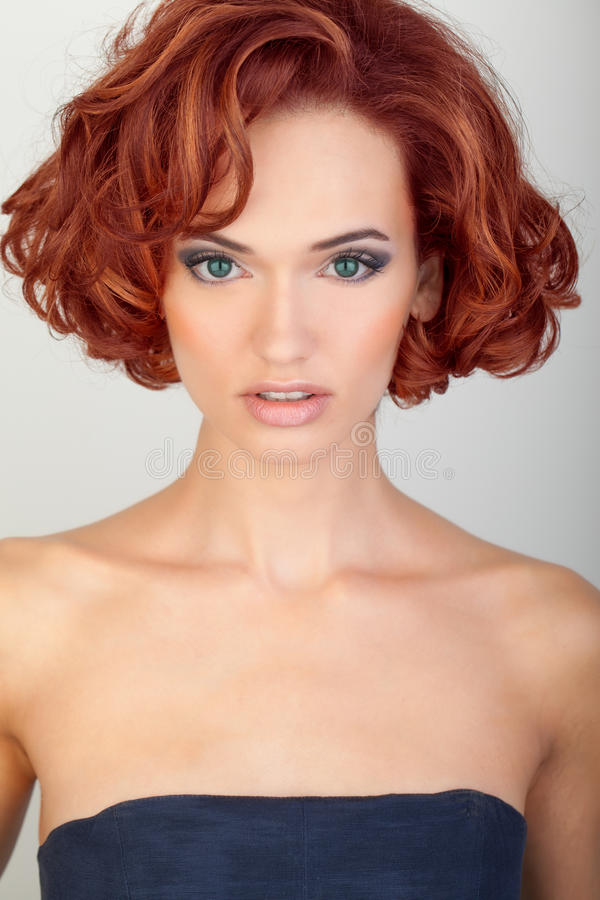 Beautiful young woman with red hair. Green eyes stock image
