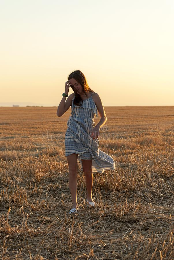 Beautiful young woman posing in a field wearing a blue and white dress, at sunset on a summer day. Red-haired. Teenager royalty free stock photography
