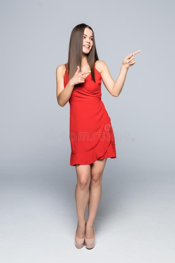Full length of Beautiful young woman in red dress and high heels is standing, presenting at something and looking away isolated on stock photo
