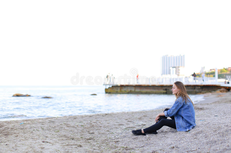 Beautiful young woman relaxes sitting on beach and enjoys view o royalty free stock images