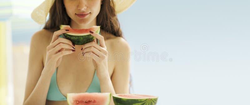 Beautiful woman eating watermelon at the beach royalty free stock photos