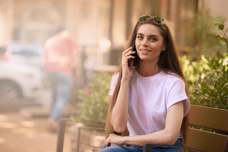 Beautiful young woman relaxing on the bench and making a call stock photo