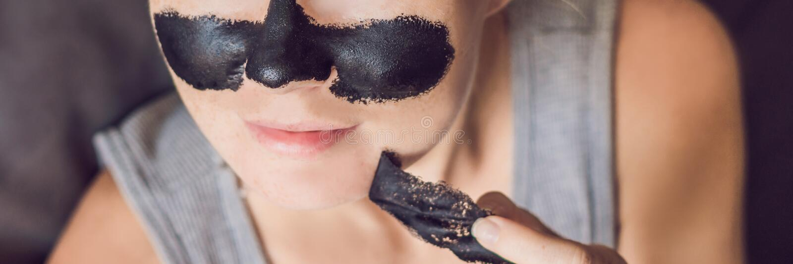 Beautiful young woman relaxing with face mask at home. Happy joyful woman applying black mask on face BANNER, long format. Beautiful young woman relaxing with stock images