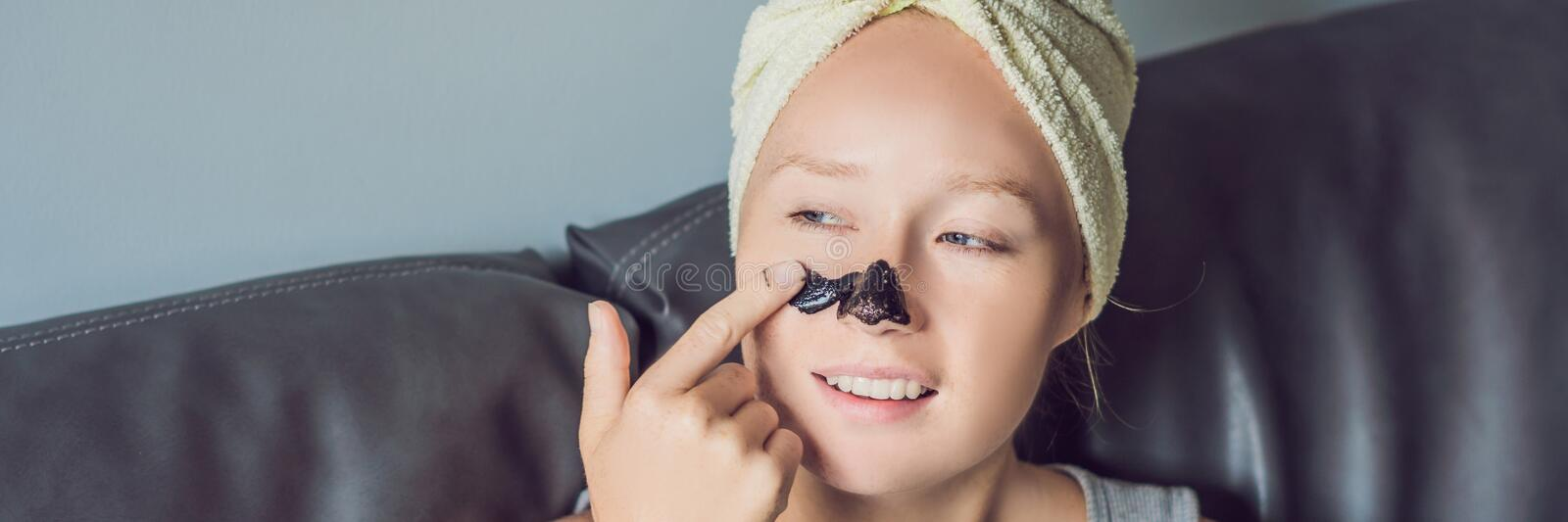 Beautiful young woman relaxing with face mask at home. Happy joyful woman applying black mask on face BANNER long format. Beautiful young woman relaxing with stock photos