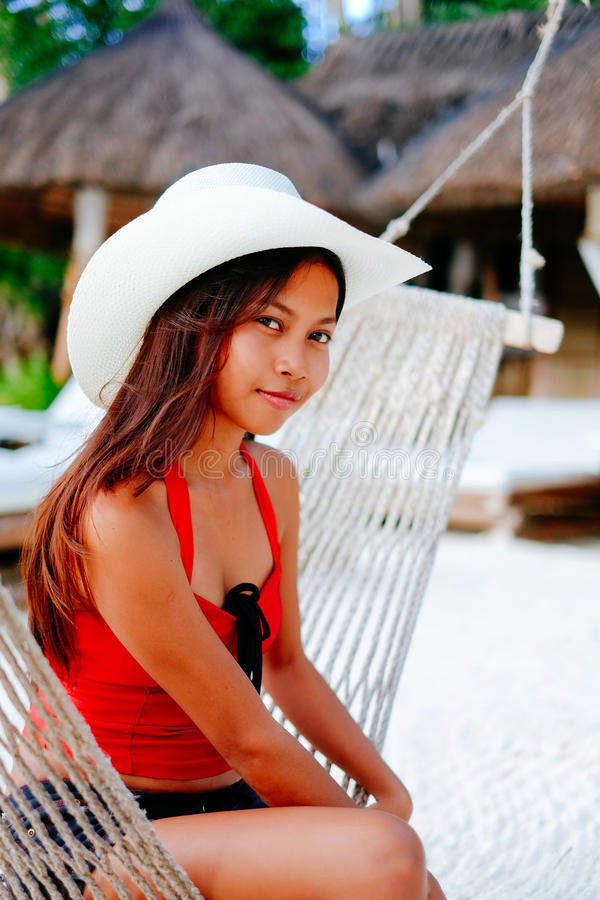 Beautiful young woman relaxing on hammock on the white sand beach during travel vacation stock photography