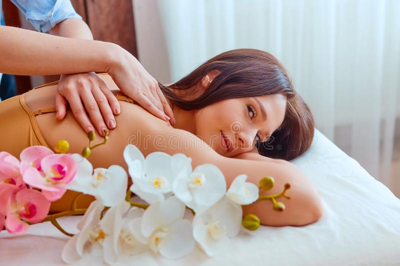Beautiful young woman relaxing with hand massage at beauty spa stock photos