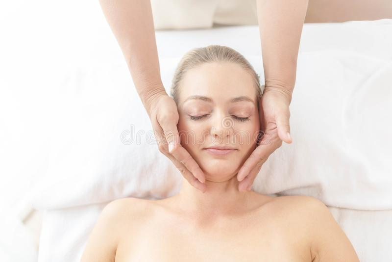 Beautiful young woman relaxing with hand massage at beauty spa. Face massage. Closed up of young beautiful woman getting spa stock image