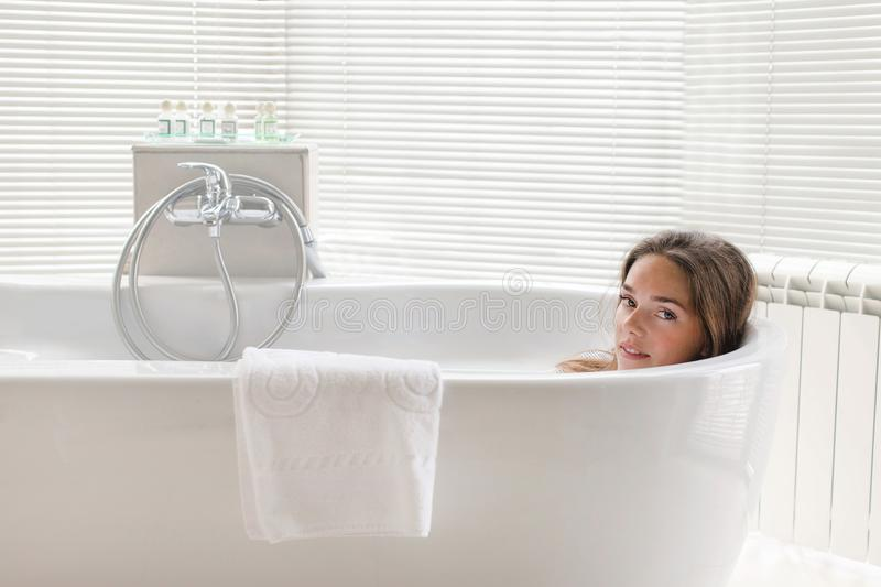 Beautiful young woman relaxing lying in bathtube royalty free stock photos