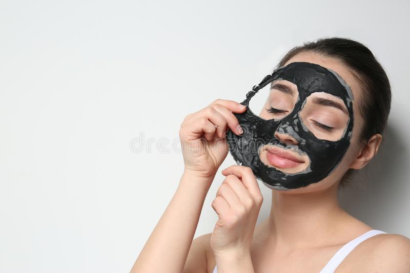 Beautiful young woman removing black mask from her face on white background. Space for text royalty free stock photos