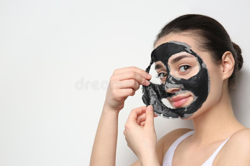 Beautiful young woman removing black mask from her face on white background. Space for text royalty free stock photo