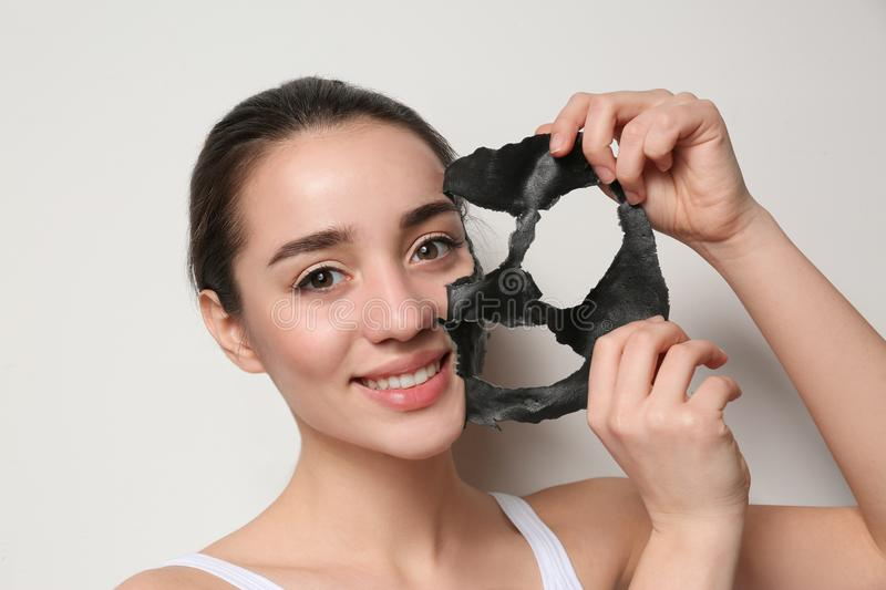 Beautiful young woman removing black mask from her face on white. Background stock images