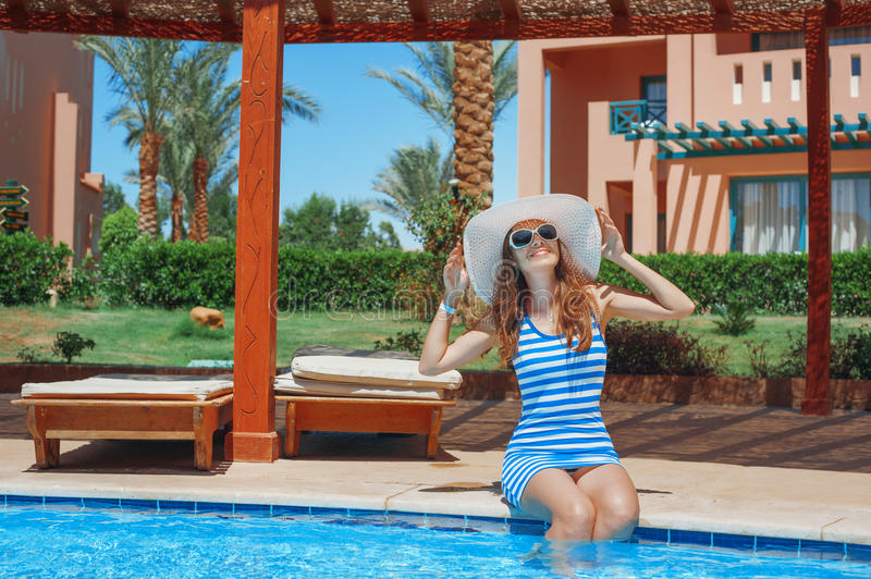 Beautiful young woman at the resort sits on the edge of the pool.  stock photography