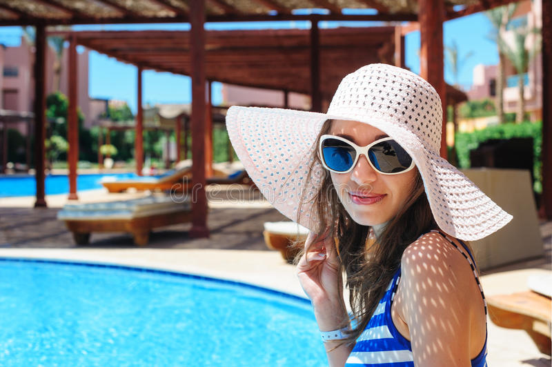 Beautiful young woman at the resort sits on the edge of the pool.  royalty free stock images