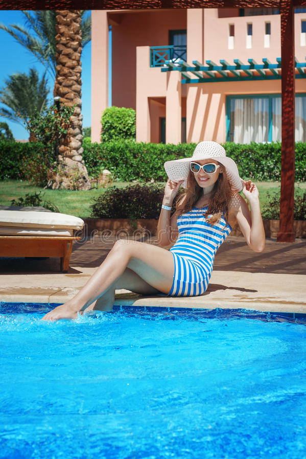 Beautiful young woman at the resort sits on the edge of the pool.  stock image